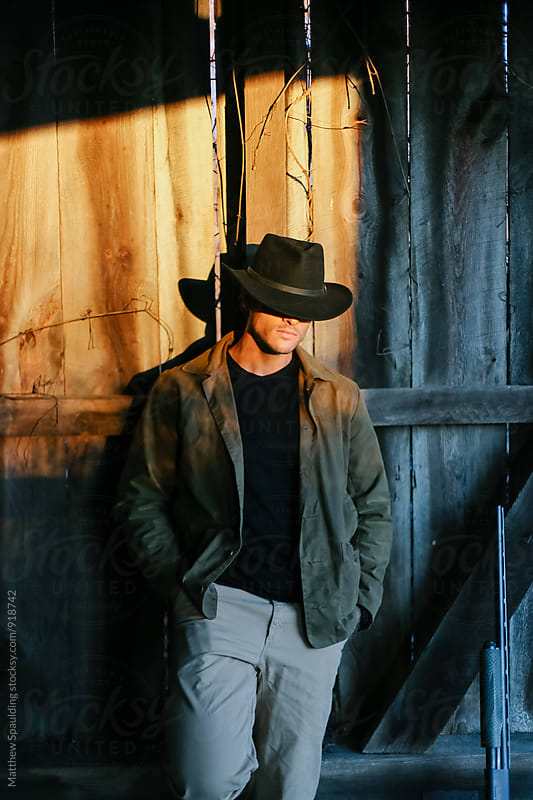 Man with gun wearing black cowboy hat leaning agains barn wood in sunlight by Matthew Spaulding for Stocksy United