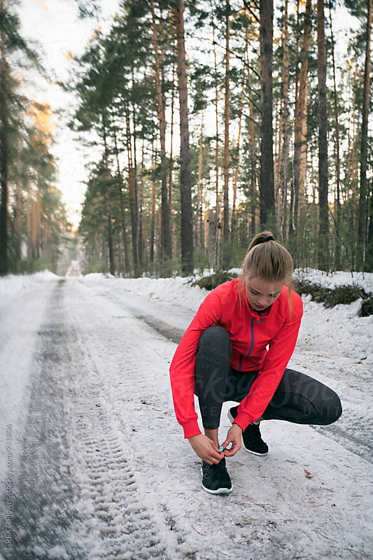 Sportswoman tying laces in snowy forest  by Danil Nevsky for Stocksy United