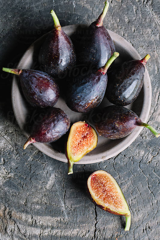 Fresh figs on wooden table by Alberto Bogo for Stocksy United