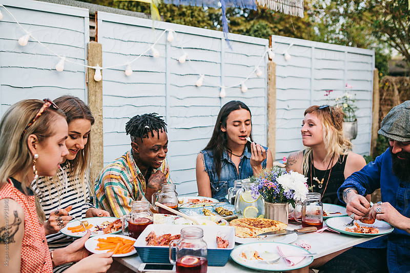Group of young people having lunch and soft drinks in a garden party by kkgas for Stocksy United