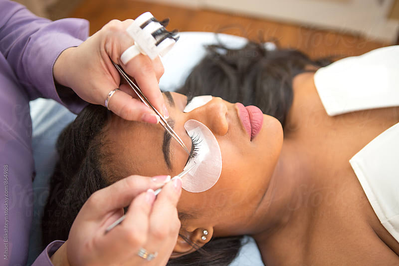 Lash technician gluing a temporary fake lash to a young black woman by Mihael Blikshteyn for Stocksy United