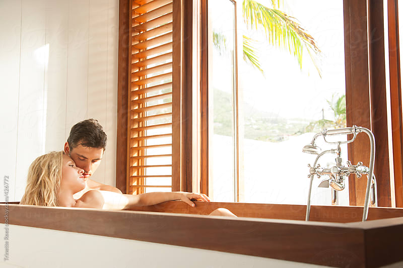Couple relaxing in bathtub at luxury resort by Trinette Reed for Stocksy United