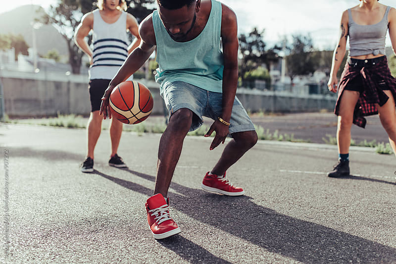 Young man playing basketball with group of friends by Jacob Ammentorp Lund for Stocksy United