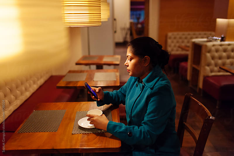 Young woman using mobile phone at a cafe by Saptak Ganguly for Stocksy United