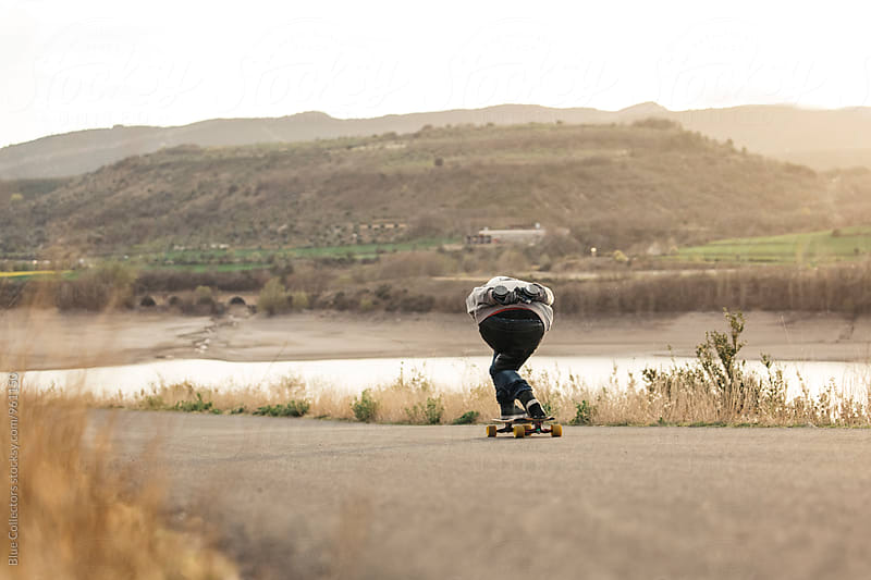 Young Man Longboarding in the road sunset by Jordi Rulló for Stocksy United