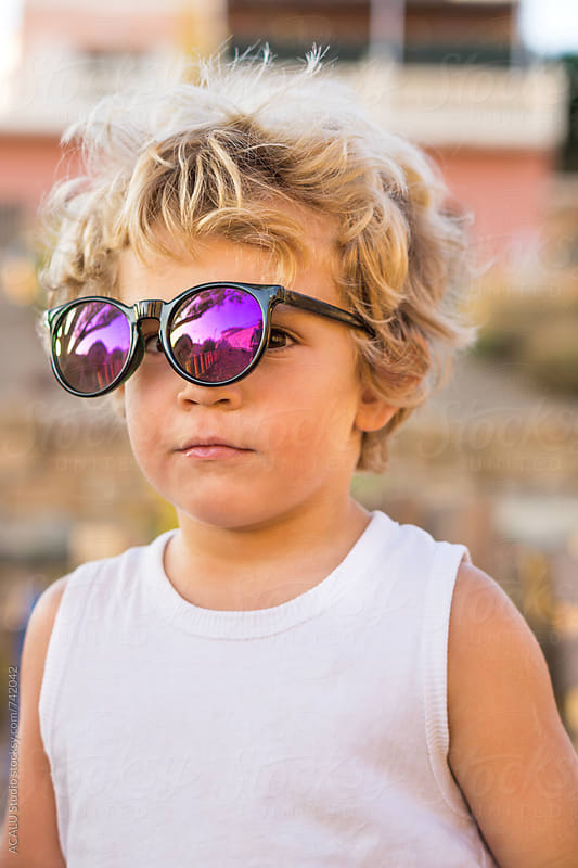 Small blond boy with sunglasses looking serious by ACALU Studio for Stocksy United