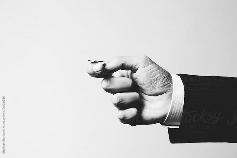 Hand of a business man in suit about to toss a coin. by Shikhar Bhattarai for Stocksy United