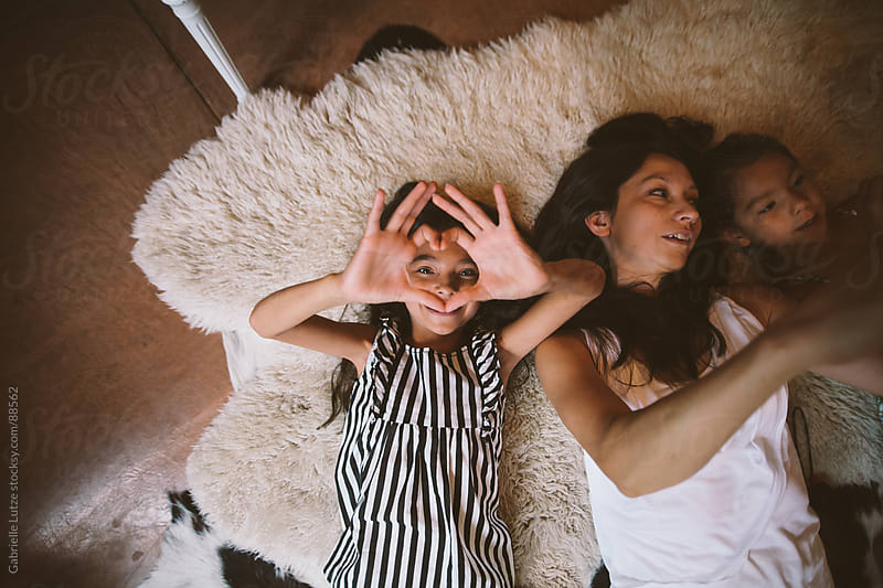 Mother and Daughters Lying Down by Gabrielle Lutze for Stocksy United