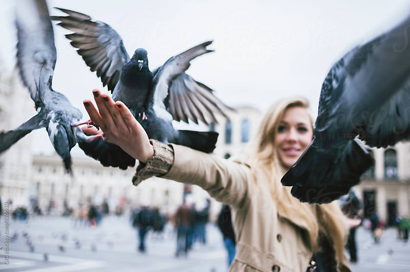 Young woman feeding pigeons in the city by Simone Becchetti for Stocksy United