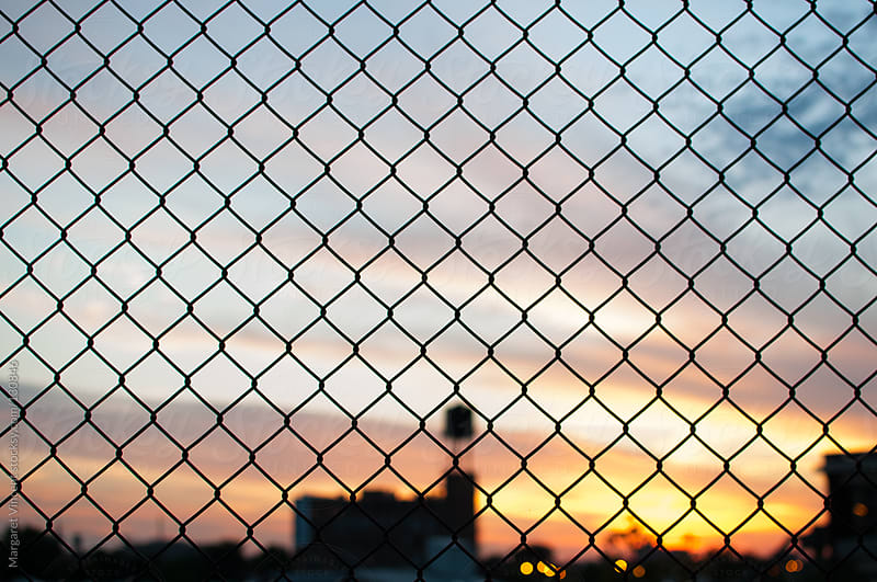 a city sunset through a chain-link fence by Margaret Vincent for Stocksy United