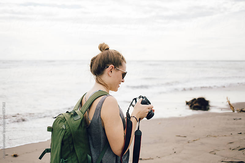 Female traveller with her camera on the beach by Koen Meershoek for Stocksy United