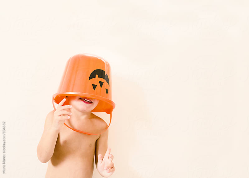 boy with halloween bucket on head by Maria Manco for Stocksy United