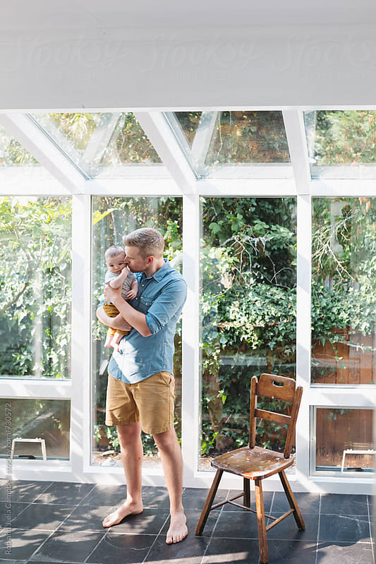 Young man kissing baby in sun room by Rob and Julia Campbell for Stocksy United