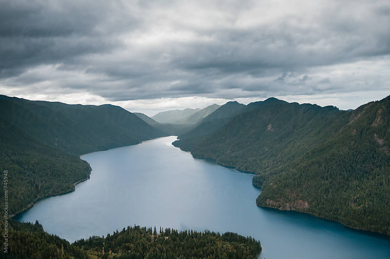 Aerial view of a large mountain lake surrounded my mountains with a cloudy sky by Mihael Blikshteyn for Stocksy United