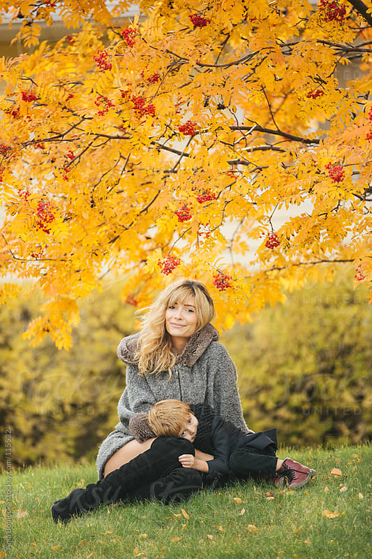 A mother and son sitting underneath a mountain ash tree looking cozy by Ania Boniecka for Stocksy United