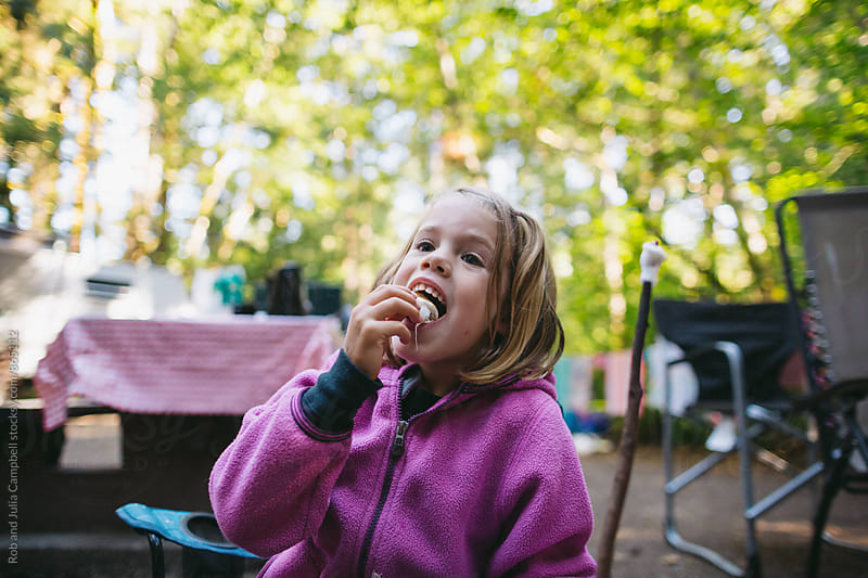Cute little girl eating marshmallow by Rob and Julia Campbell for Stocksy United