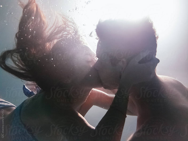 Young couple have fun during a night party underwater by GIC for Stocksy United