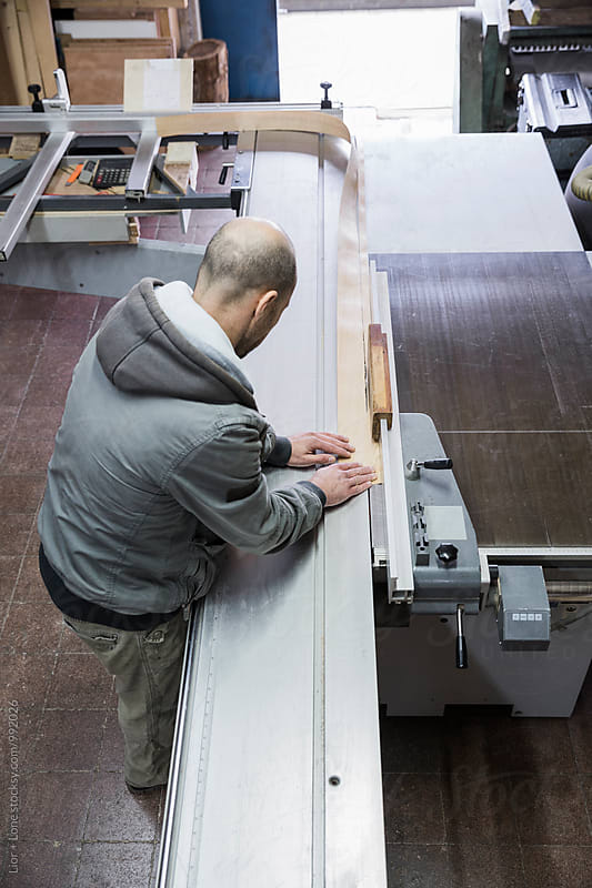 Carpenter trimming a sheet of wood using industrial table saw by Lior + Lone for Stocksy United