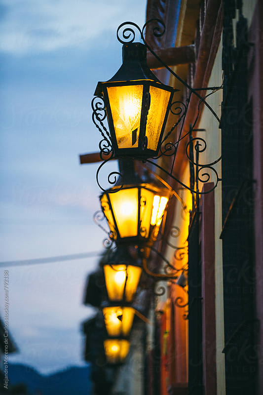 Outdoor iron lantern lampposts on the exterior of a traditional village at dusk by Alejandro Moreno de Carlos for Stocksy United