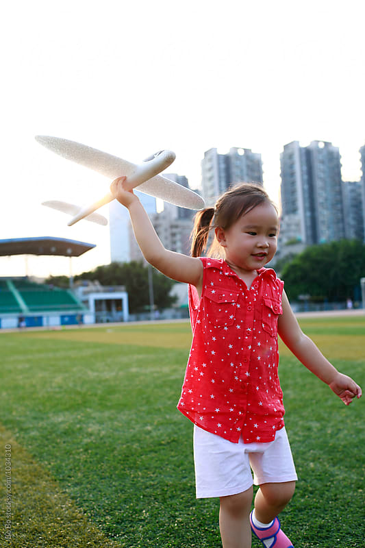 little asian girl playing with her plane toy in the football field by Bo Bo for Stocksy United