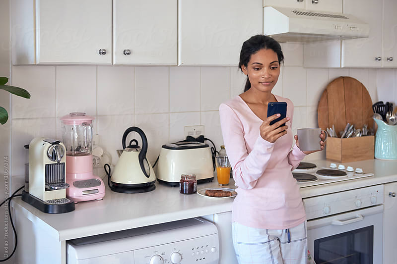 Hispanic woman with phone in kitchen by Daxiao Productions for Stocksy United