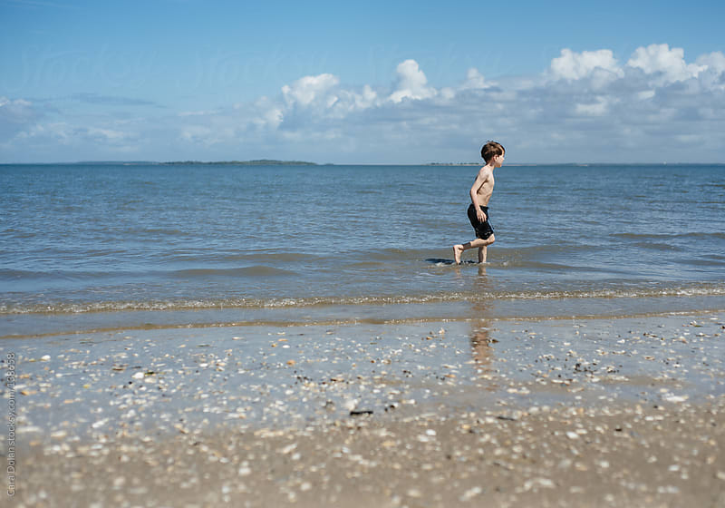 Boy runs and splashes in the water at a beach in summer by Cara Dolan for Stocksy United