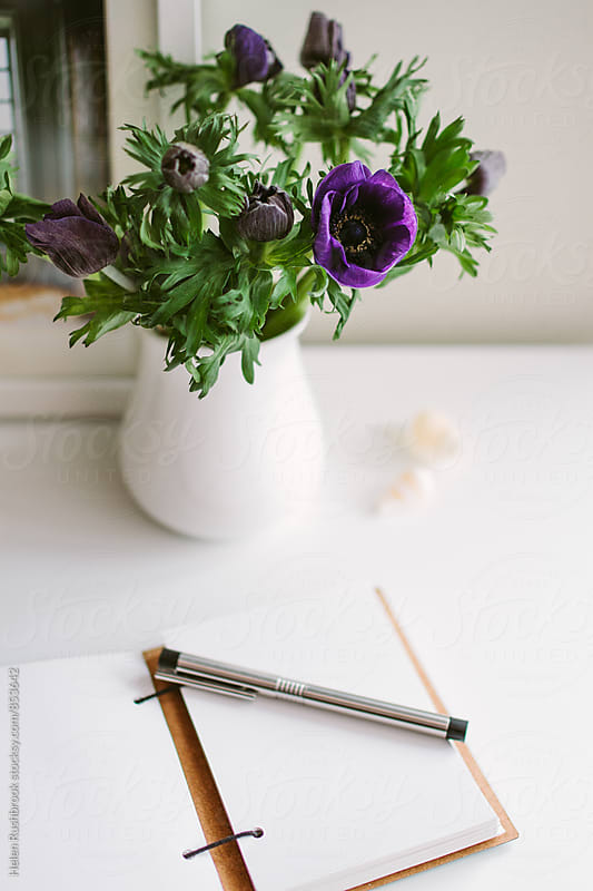 A jug of anemones on a white table with a journal open at a blank page. by Helen Rushbrook for Stocksy United