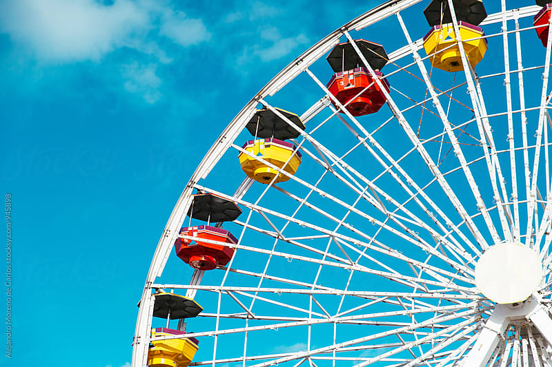 Detail of colourful ferris wheel against blue sky by Alejandro Moreno de Carlos for Stocksy United