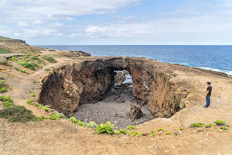 Man on the edge of a big hole in the ground next to the sea by ACALU Studio for Stocksy United