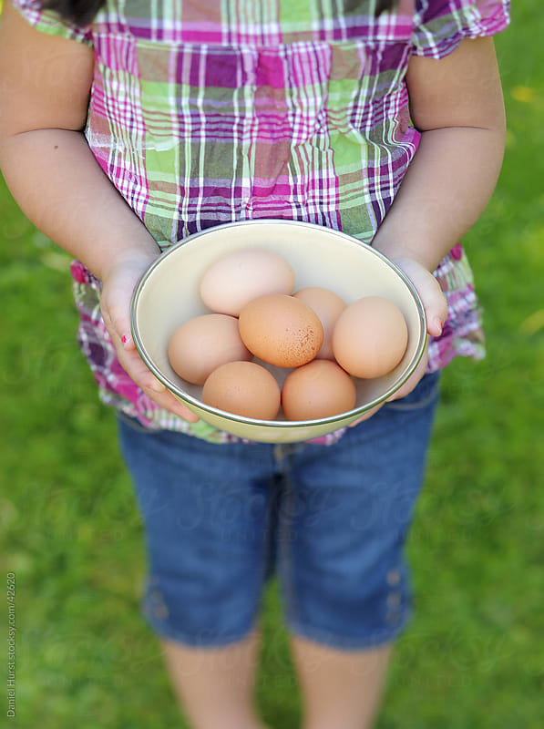 Young girl holding bowl of eggs by Daniel Hurst for Stocksy United
