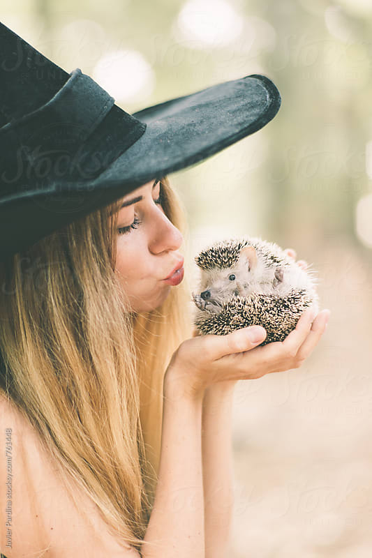 girl in a witch costume playing with a hedgehog by Javier Pardina for Stocksy United