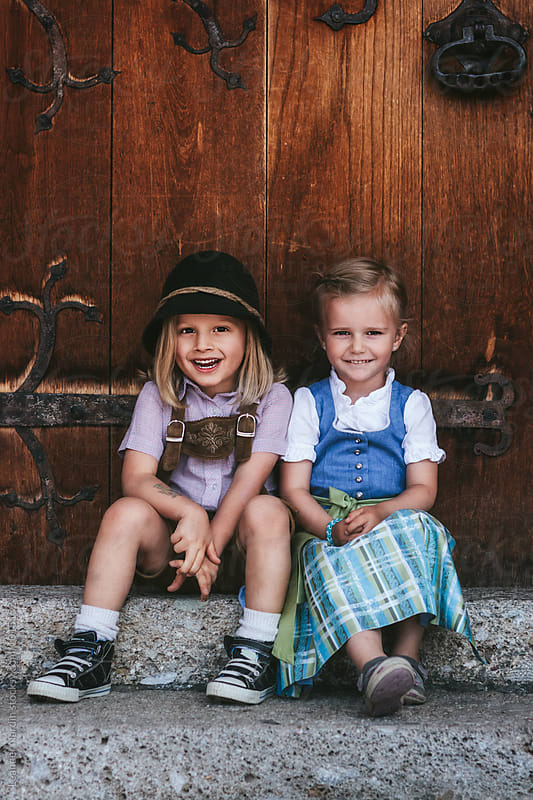 cute smiling children couple in typical austrian outfit sitting in front of wooden door by Leander Nardin for Stocksy United
