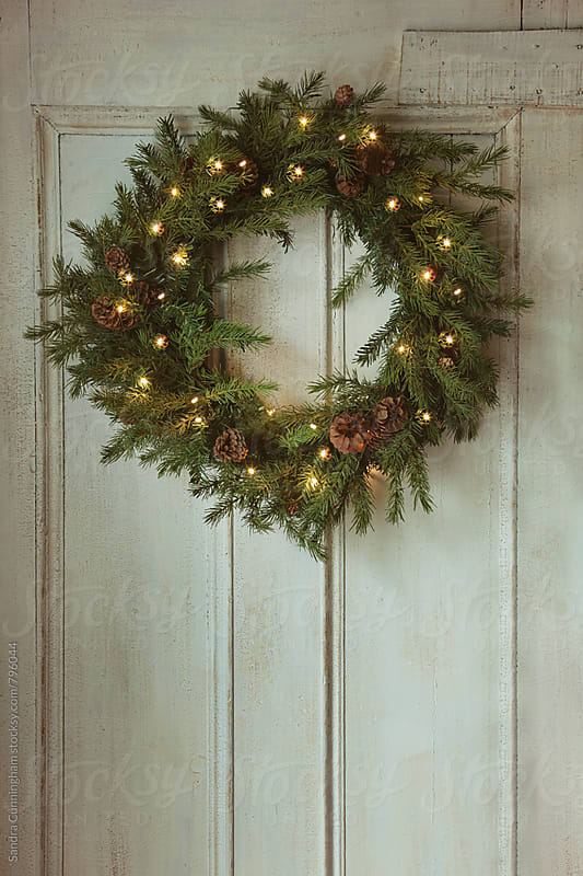 Christmas wreath with lights on vintage door by Sandra Cunningham for Stocksy United
