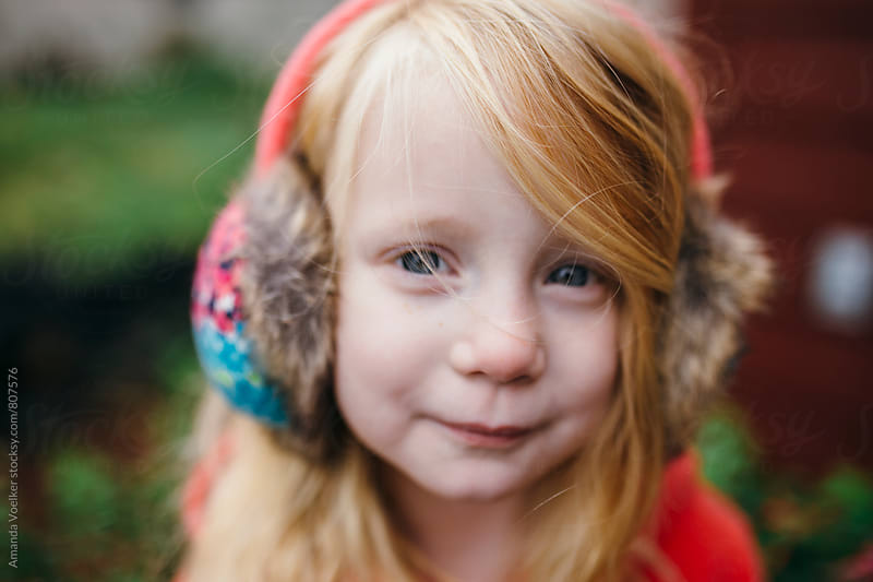 Sweet Portrait of a Little Girl with Earmuffs by Amanda Voelker for Stocksy United