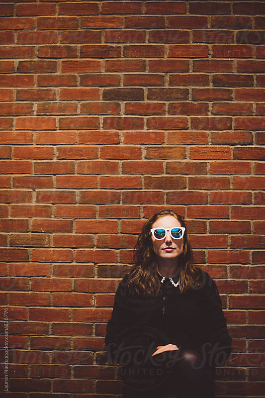 Young woman sitting in front of brick wall by Lauren Naefe for Stocksy United