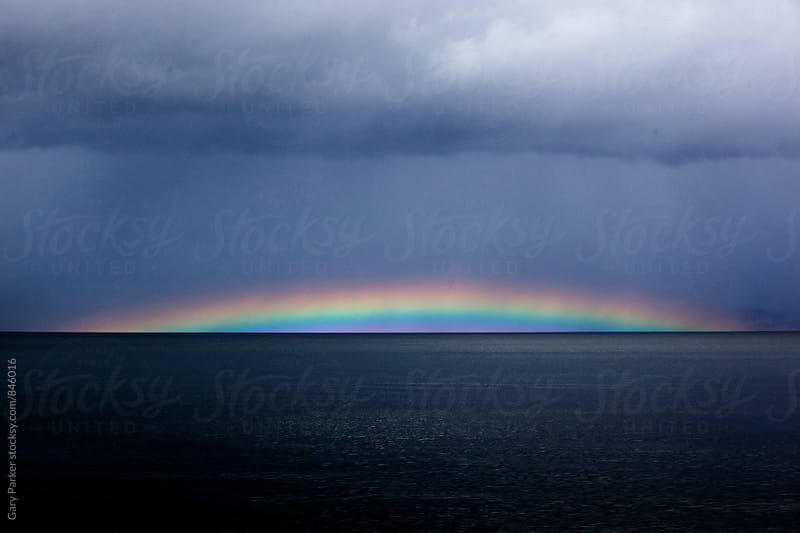 Rainbow over a dark sea by Gary Parker for Stocksy United