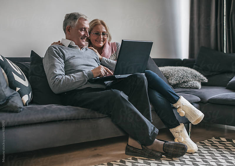 Senior Couple Sitting in the Living Room With Laptop by Mosuno for Stocksy United