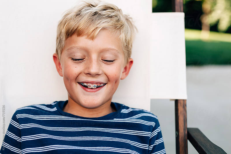portrait of a happy, laughing boy with braces  by Kelly Knox for Stocksy United