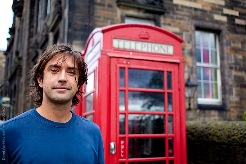 Young man standing in front of an old typical British phone booth by Denni Van Huis for Stocksy United