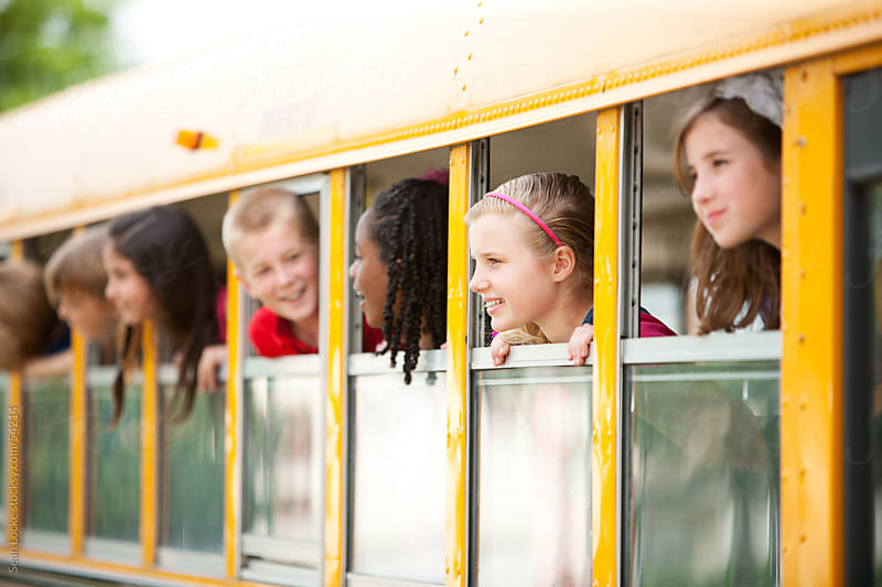 School Bus: Kids Peering Out Bus Window by Sean Locke for Stocksy United