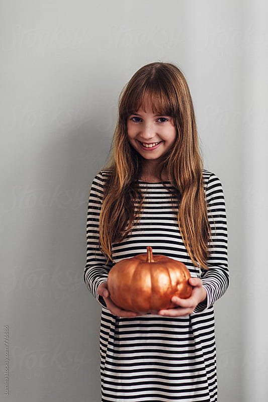 Smiling Girl Holding a Pumpkin  by Lumina for Stocksy United