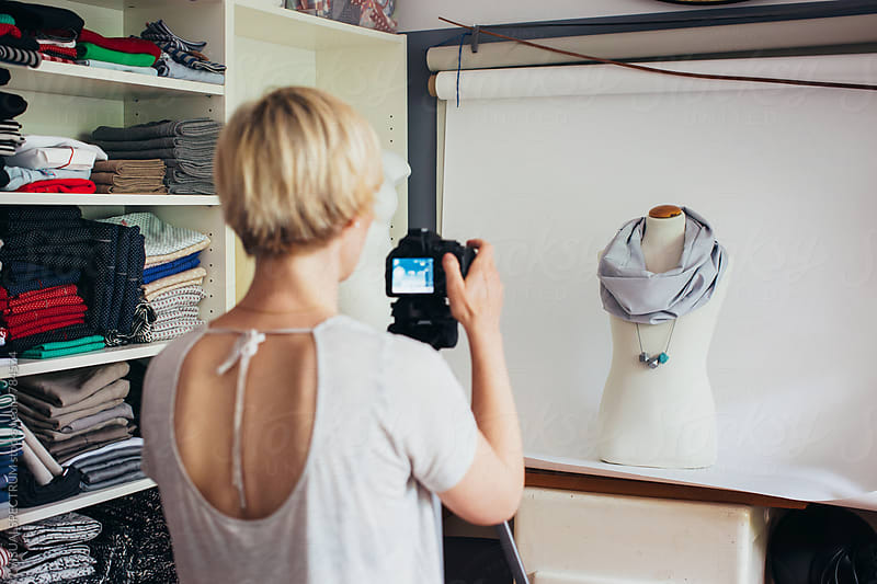 Female Fashion Designer Photographing Scarf on Display Dummy in Bright Atelier by VISUALSPECTRUM for Stocksy United