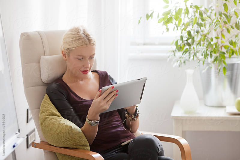 Caucasian Woman Using a Tablet by Lumina for Stocksy United