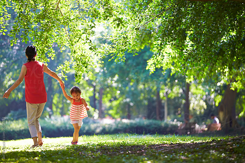 little girl playing with her mother outdoor in the sunny park by Bo Bo for Stocksy United