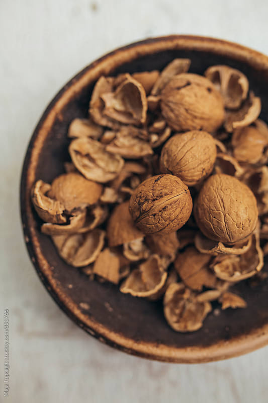 Cracked walnuts on a plate by Maja Topcagic for Stocksy United