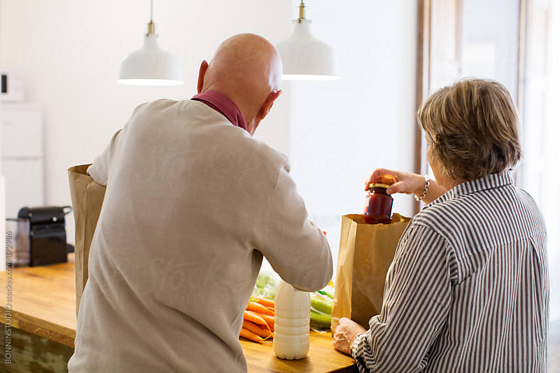Elderly couple unpacks healthy market food in their kitchen. by BONNINSTUDIO for Stocksy United