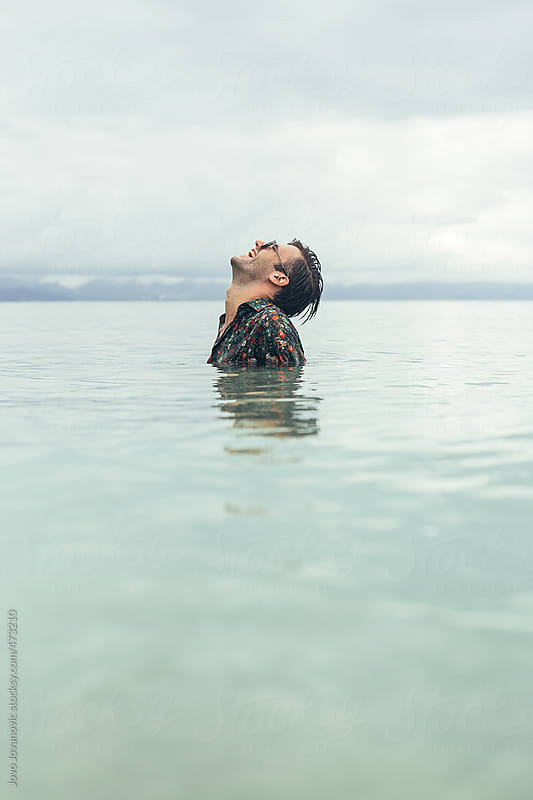 Crazy young man laughing and standing in ocean with clothes and sunglasses on by Jovo Jovanovic for Stocksy United
