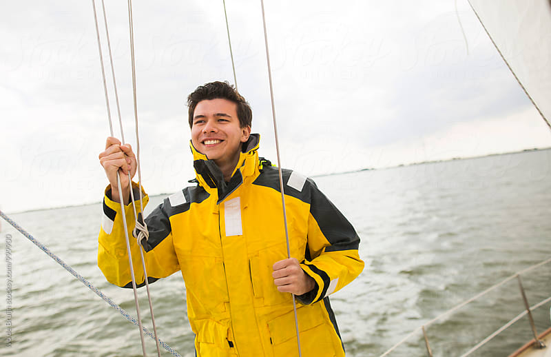 Young man on a wooden sailboat, wearing a yellow sailing jacket. by Ivo de Bruijn for Stocksy United