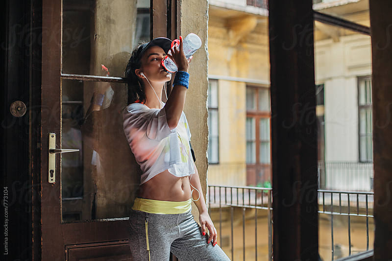 Young Woman in Sportswear Drinking Water by Lumina for Stocksy United
