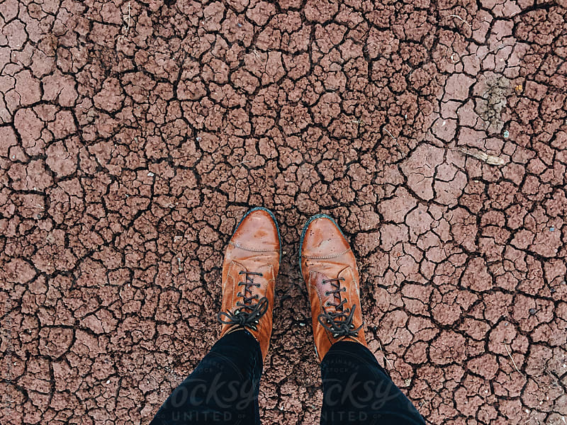 leather boots standing on a cracked, red, clay ground by KATIE + JOE for Stocksy United